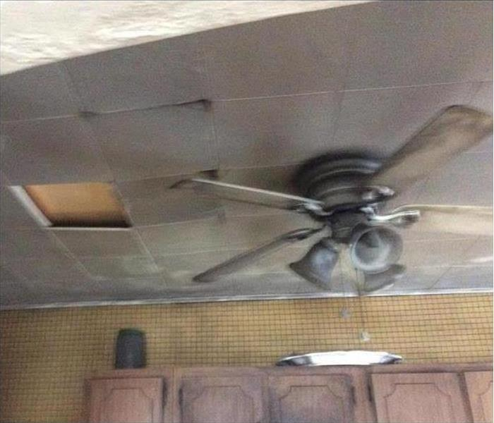 Picture of a fan and ceiling with soot damage after a fire